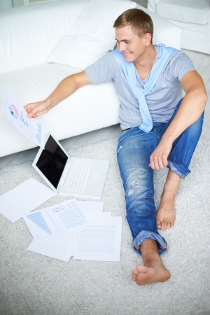 barefoot man: Image of young guy in casual sitting on the floor and looking at paper in his hand