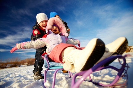 Friendly kids in winterwear riding on sledge outside Stock Photo - 24068797