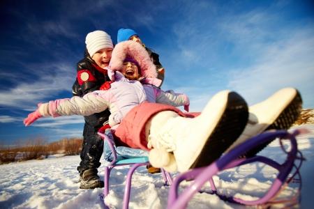 winterwear: Friendly kids in winterwear riding on sledge outside Stock Photo