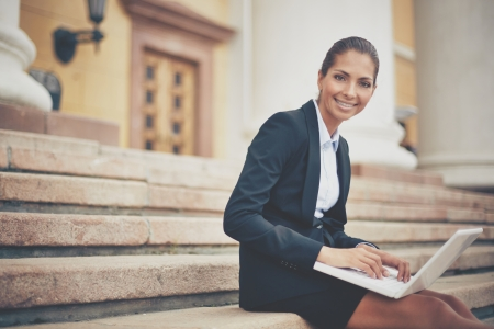 laptop outside: Image of young businesswoman with laptop looking at camera while networking on steps of building