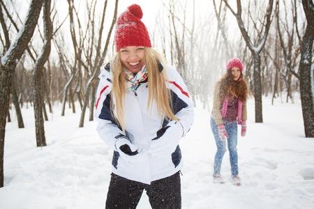 winterwear: Portrait of happy girl in winterwear laughing on background of her friend outside Stock Photo