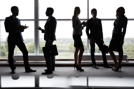 Several colleagues communicating at meeting in office