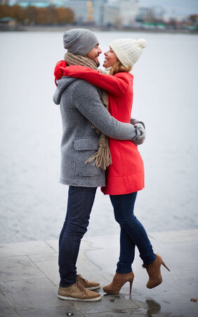 hugging couple: Portrait of happy dates in coats embracing outdoors