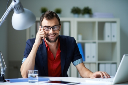 man working: Handsome businessman speaking on the phone and working with laptop in office