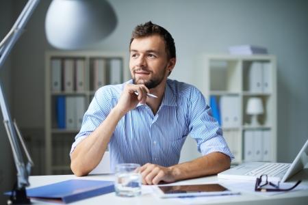 trabajo en oficina: Hombre de negocios elegante que piensa en algo en la oficina Foto de archivo