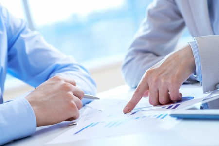project manager: Close-up of female hand pointing at business document in working environment Stock Photo