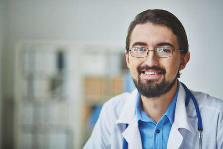 young male doctor: Portrait of smiling male practitioner looking at camera