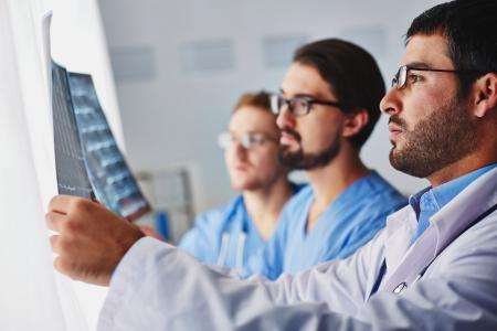 Portret van jonge mannelijke artsen kijken naar x-ray Stockfoto