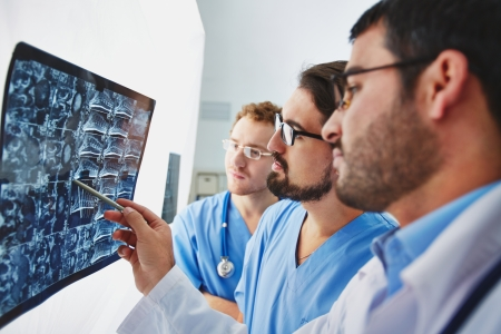 clinician: Young male doctors looking at x-ray and analyzing it Stock Photo