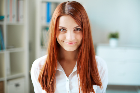 Happy girl with long ginger hair looking at camera photo