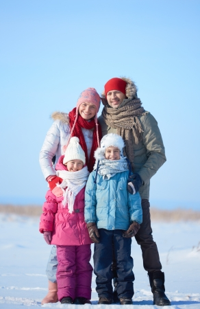 winterwear: Happy parents and their kids in winterwear looking at camera outside