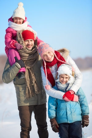 winterwear: Happy parents with kids in winterwear looking at camera outside