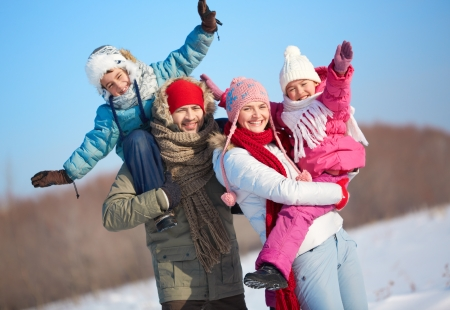 winterwear: Happy parents holding kids in winterwear and looking at camera outside Stock Photo