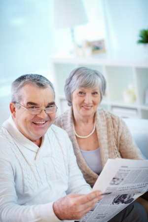 newspaper reading: Portrait of mature man reading newspaper at home with his wife near by