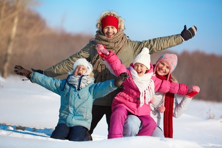 winterwear: Happy parents and their kids in winterwear having fun outside Stock Photo