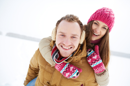 winterwear: Portrait of happy young couple having fun in winter park