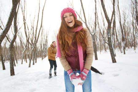 winterwear: Portrait of happy girl in winterwear laughing on background of her boyfriend outside