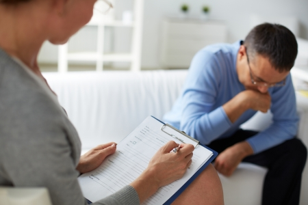 career counseling: Female psychologist consulting pensive man during psychological therapy session