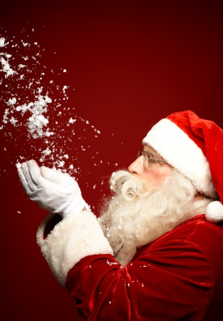 Photo of Santa Claus blowing snow over red