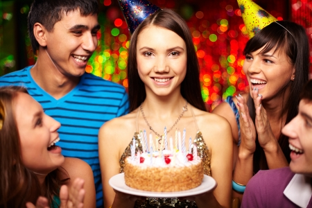 Portrait of joyful girl with birthday cake surrounded by friends at party photo
