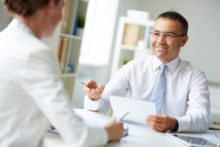성숙한 사업가 사무실에서 그녀에게 말하는 동안 그의 동료를보고