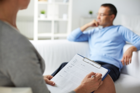 Psicólogo Mujer tomando notas durante la sesión de terapia psicológica Foto de archivo