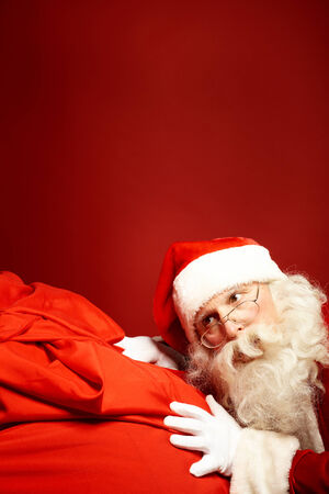 hark: Portrait of Santa Claus leaning over huge red sack Stock Photo
