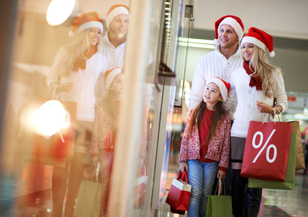 Portrait of happy family in Santa caps looking at shop window in the mall