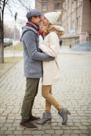 Portrait of happy dates in coats embracing outdoors photo