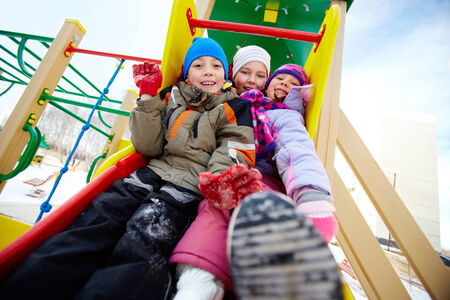 Happy friends in winterwear having fun on playground photo