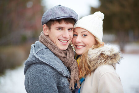 Portrait of happy guy and his girlfriend looking at camera outside photo