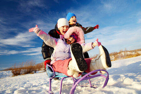 Friendly kids in winterwear riding on sledge outside photo