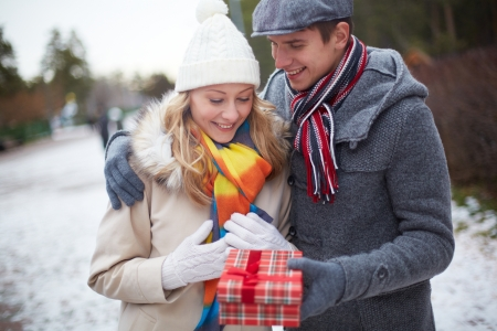 Image of affectionate guy giving his girlfriend Christmas present outside photo