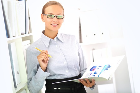 Portrait of elegant businesswoman looking at camera while working with papers in office photo