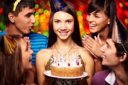 Portrait of joyful girl with birthday cake surrounded by friends at party Stock Photo - 24320314
