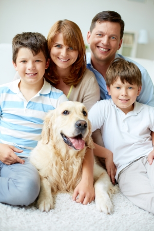 Portrait of happy family with their pet looking at camera photo