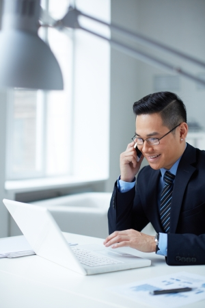 Young businessman in formalwear using laptop and calling in office photo