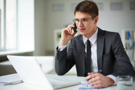 Young businessman in suit using laptop and calling in office photo