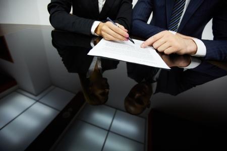 contrato de trabajo: Imagen de manos humanas durante la lectura del contrato