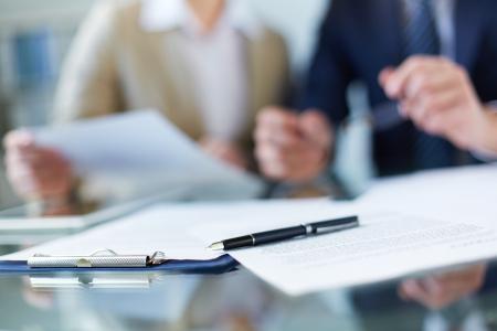Los documentos de negocios y la pluma en el lugar de trabajo