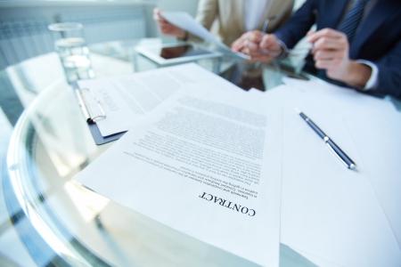 contrato de trabajo: Los documentos de negocios y la pluma en lugar de trabajo con la gente que trabaja en el fondo Foto de archivo