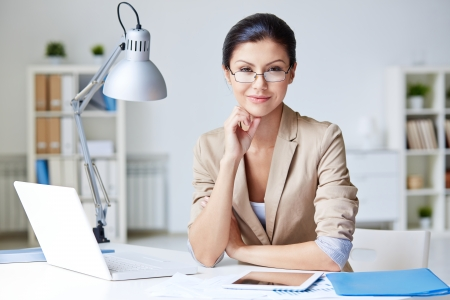 Smart businesswoman in formalwear looking at camera in office photo