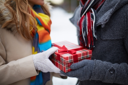 relationship love: Image of gloved hand of guy giving his girlfriend Christmas present