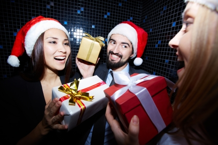 company party: Portrait of joyful colleagues in Santa caps holding Crhistmas gifts in nightclub  Stock Photo