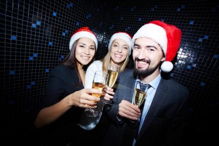 brindisi spumante: Ritratto di colleghi gioiosi in Santa tappi brindando con champagne in discoteca