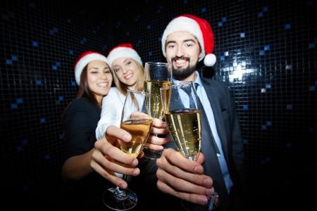 brindisi spumante: Tre partner commerciali in Santa tappi brindando con champagne in discoteca Archivio Fotografico