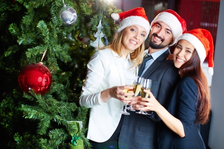 occasion: Portrait of joyful colleagues in Santa caps toasting with champagne by Christmas tree  Stock Photo