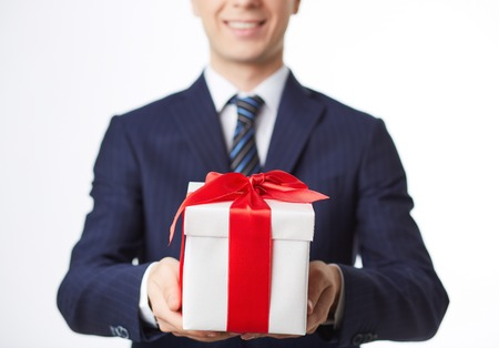 Image of giftbox held by smiling businessman photo