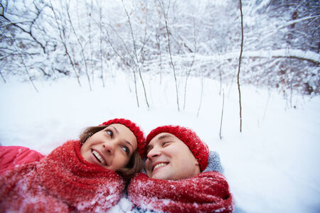 winterwear: Portrait of happy young couple lying on snow in winter park and looking at one another