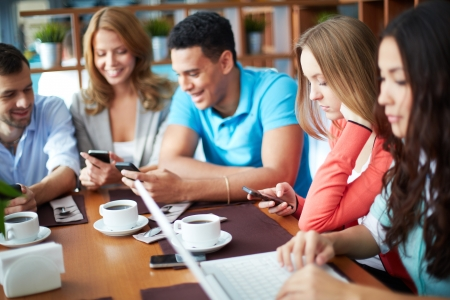 tomando café: Retrato de amigos adolescentes utilizando aparatos modernos, mientras que sentado en la cafetería